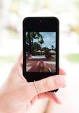 Die Hand der Frau mit dem Mobiltelefon, das selfie von ihr nimmt Stockfotos