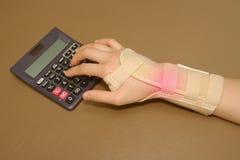 Die Hand der Frau mit der Handgelenkunterstützung, die Berechnungen tut Stockfoto