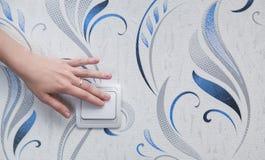 Die Hand der Frau schalten die Lichter ein lizenzfreies stockfoto