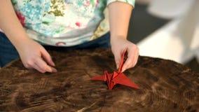 Die Hand der Frau setzt einen Papierkran auf dem Tisch stock video footage