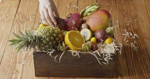Die Hand der Frau setzte Holzkiste mit Zusammenstellung von exotischen frischen organischen Früchten auf einen Holztisch Bewegung stock video footage
