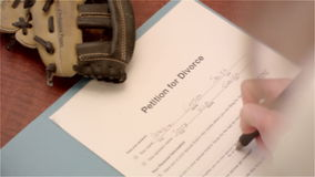 Die Hand der Frau unterzeichnet Scheidungspapiere mit Baseballhandschuh des Kindes im Schuss stock video footage