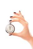 Die Hand der Frauen mit Stoppuhr, Nägel bedeckt mit AuberginenNagellack stockfotos