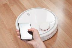 die Hand der Frauen unter Verwendung des Mobiles, zum des weißen Roboterstaubsaugers zu steuern moderne intelligente Reinigungste lizenzfreie stockbilder