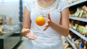 Die Hand der Frauen wirft oben bunte Orange im Supermarkt in slowmotion stock video footage