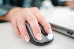 Die Hand der Geschäftsfrau, die eine Computermaus hält Stockfotografie