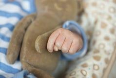 Die Hand der gestreiften Klage des Babys Stockfoto