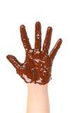 Die Hand der Kinder befleckt mit dem Schokoladenbereifen. stockbild