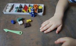 Die Hand der Kinder, die eine Zahl von der Knetmasse hält Stockfotografie
