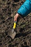 Die Hand der Kinder, die mit einer Gartenspachtel arbeitet lizenzfreie stockfotografie