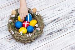 Die Hand der Kinder nimmt farbige Ostereier von einem Nest auf einem weißen hölzernen Hintergrund, Ostern-Feiertag, Kopienraum, A stockfotos