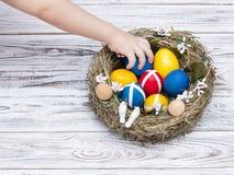 Die Hand der Kinder nimmt farbige Ostereier von einem Nest auf einem weißen hölzernen Hintergrund, Ostern-Traditionen zu Ehren de lizenzfreies stockfoto