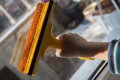 Die Hand der Kinder wäscht das Fenster mit einem Wischer lizenzfreie stockfotos