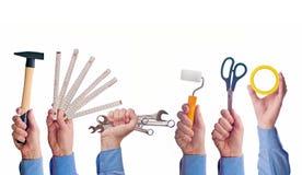 Die Hand der männlichen Arbeitskraft, die verschiedene Handwerkshandelswerkzeuge hält Lizenzfreie Stockfotografie
