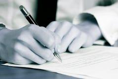 Die Hand der Person, die ein Dokument unterzeichnet Stockbild
