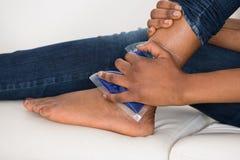 Die Hand der Person, die Eis-Gel-Satz auf Knöchel hält Lizenzfreie Stockfotografie