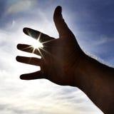 Die Hand der Person, die in Richtung zum Himmels-Sonnenlicht erreicht Lizenzfreie Stockbilder
