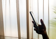 Die Hand der Person, die zuhause einen Handy, neben einem Fenster hält stockbilder