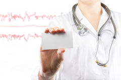 Die Hand der Ärztin, die leere Visitenkarte hält Schließen Sie herauf Schuss auf medizinischem unscharfem Hintergrund Konzept des Lizenzfreie Stockfotografie