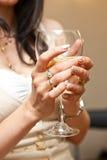 Die Hand der Schönheit, die ein Glas Weißwein hält Stockfoto