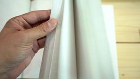 Die Hand des asiatischen Mannes öffnet das Notizbuch auf dem Holztisch stock footage