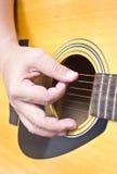 Die Hand des asiatischen Mannes, die Akustikgitarre spielt. Lizenzfreie Stockfotos