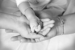 Die Hand des Babys nach ihrer Elternteilhand stockfotos