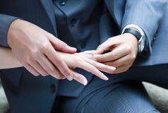 Die Hand des Bräutigams, die einen Ehering setzt Lizenzfreies Stockfoto