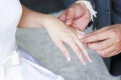 Die Hand des Bräutigams, die einen Ehering setzt Lizenzfreie Stockfotos