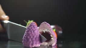 Die Hand des Chefs schneidet den dekorativ-förmigen Kuchen mit der inneren Füllung, frische Früchte liegen nahe bei ihr, das Proz stock video footage