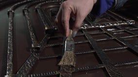 Die Hand des Dekorateurs malt ein schönes, exklusives geschmiedetes Produkt stock video