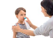 Die Hand des Elternteils eines Mädchens wendet ein lokalisiertes Nasenspray an Stockbild
