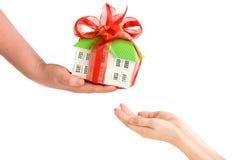 Die Hand des Erwachsenen, die Kinderhänden ein Modell des Hauses gibt Lizenzfreie Stockbilder
