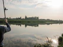 Die Hand des Fischers wirft eine Angelrute in der Ruhe des Morgens nahe dem See Lizenzfreie Stockfotografie