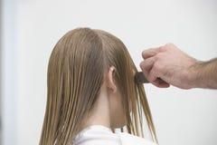 Die Hand des Friseurs, die das nasse Haar des Kunden am Salon kämmt Stockbild