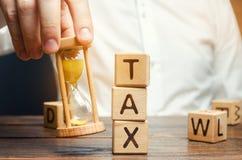 Die Hand des Geschäftsmannes, die eine Sanduhr nahe den Holzklötzen mit der Wort Steuer hält Zeit, Steuern zu zahlen Das Konzept  lizenzfreies stockfoto