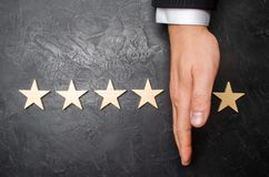 Die Hand des Geschäftsmannes trennt den fünften Stern von den anderen vier Der Verlust des fünften Sternes, der Fall in Bewertung Stockbilder