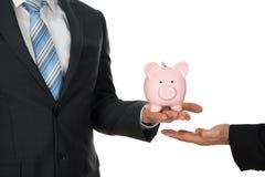 Die Hand des Geschäftsmannes, die piggybank hält Lizenzfreie Stockbilder