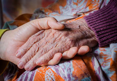 Die Hand des jungen Mädchens berührt und hält eine Hand der alten Frau Stockfotografie