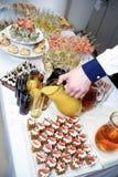 Die Hand des Kellners gießt Orangensaft von einem Krug Stockbild