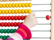 Die Hand des Kindes mit dem bunten Abakus lokalisiert Lizenzfreies Stockfoto
