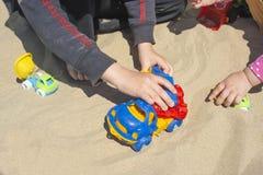 Die Hand des Kindes, die mit einem Spielzeuglastwagen im Sand spielt stockbild
