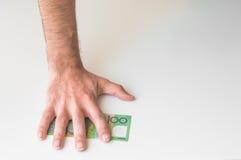 Die Hand des Mannes auf australischem Dollar Lizenzfreie Stockfotografie