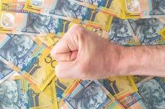 Die Hand des Mannes auf australischem Dollar Stockfotos