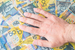 Die Hand des Mannes auf australischem Dollar Stockfotografie
