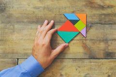 Die Hand des Mannes, die auf den Pfeil gemacht vom Tangrampuzzlespiel zeigt Lizenzfreies Stockbild