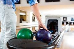 Die Hand des Mannes, die Bowlingkugel vom Gestell aufhebt Lizenzfreie Stockfotografie