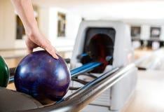 Die Hand des Mannes, die Bowlingkugel vom Gestell aufhebt Stockfoto