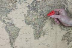 Die Hand des Mannes, die ein Papierflugzeug auf Weltkarte hält Stockfotografie