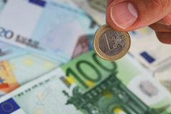 Die Hand des Mannes, die eine Euromünze auf Eurobanknoten hält Stockbilder